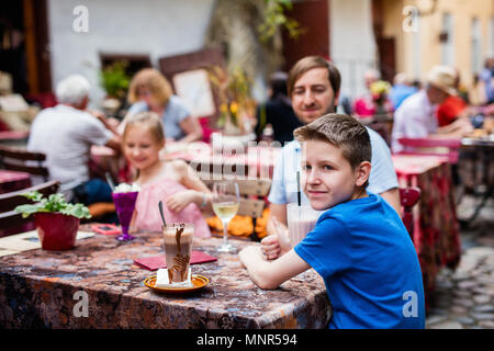 Father and his kids at outdoor cafe on summer day - Stock Photo