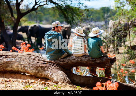 Family of father and kids on African safari vacation enjoying wildlife viewing at watering hole - Stock Photo