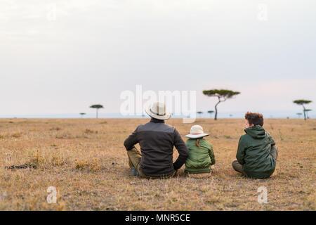 Family of father and kids on African safari vacation enjoying views over Masai Mara in Kenya - Stock Photo