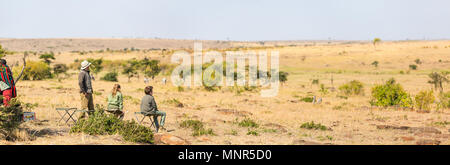 Family of father and kids on African safari vacation enjoying bush breakfast with a view - Stock Photo
