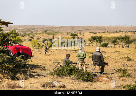 Family of father and kids on African safari vacation enjoying bush view - Stock Photo