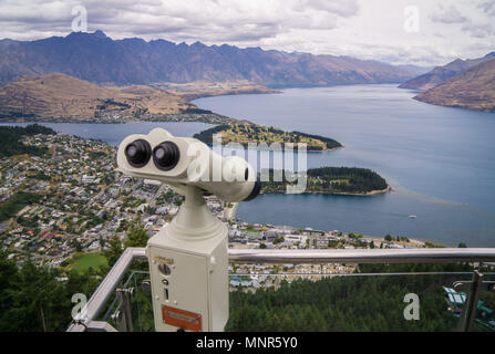 Fixed binoculars at the top of the Skyline Gondola showing the view over Queenstown and Lake Wakatipu in New Zealand - Stock Photo