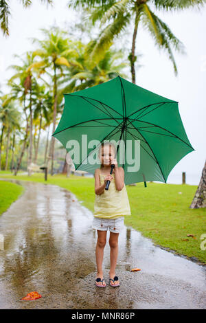 Adorable little girl with big green umbrella outdoors at rainy day