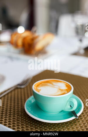 Fresh coffee in turquoise cup served for breakfast - Stock Photo