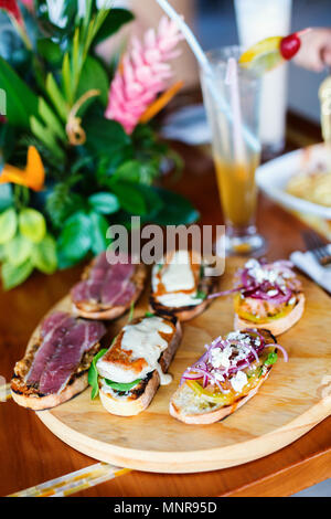 Different kinds of fresh homemade crispy Italian antipasto bruschettas - Stock Photo