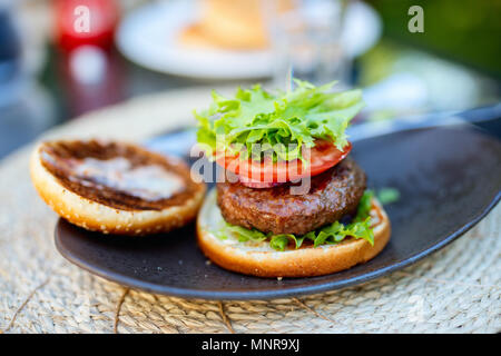 Close up assembling of delicious fresh burger with tomato and fresh green salad - Stock Photo