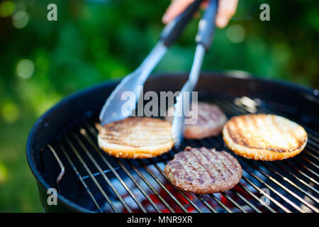 Grilling of fresh bun and burger meat cutlets for homemade burger cooking outdoors on summer day - Stock Photo