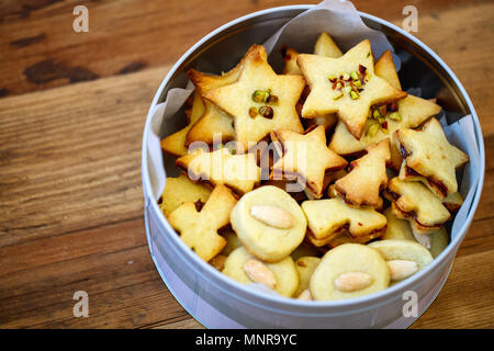 Freshly baked homemade Christmas cookies in a tin box,  wooden background - Stock Photo