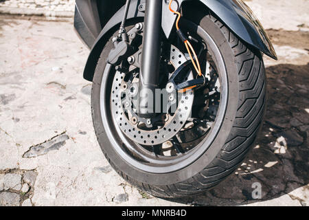 Wheel of motorcycle or scooter or moped. Autotire or tire and design of wheel of motorcycle. Brake system and spare parts for bike - Stock Photo