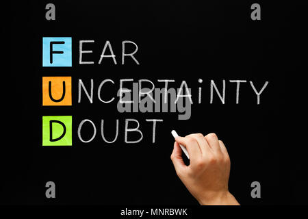 Hand writing FUD - Fear Uncertainty And Doubt with white chalk on blackboard. - Stock Photo