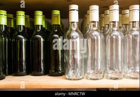 Background wall from empty bottles of wine on wooden shelve drinks - Stock Photo