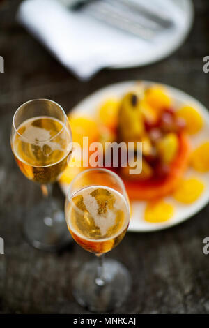 Two glasses with champagne  and fruits on wooden vintage tray served for special occasion or celebration - Stock Photo