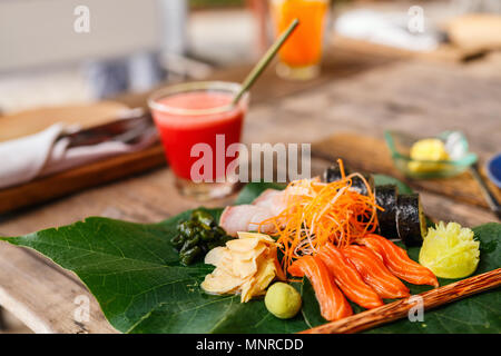 Japanese cuisine delicious sushi rolls and fresh sashimi served on a green leaf at restaurant - Stock Photo