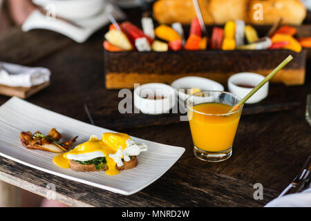 Poached eggs served for breakfast with bacon and juice - Stock Photo