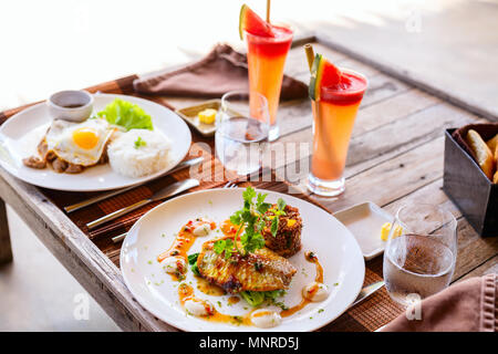 Delicious lunch for two in restaurant of fish,  rice,  fried egg and green vegetables - Stock Photo