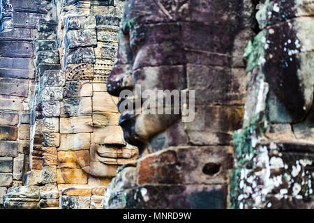 Faces of ancient Bayon temple popular tourist attraction in Angkor Thom,  Siem Reap,  Cambodia. - Stock Photo