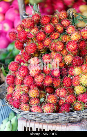 Assortment of fresh exotic rambutan fruits on market stall - Stock Photo
