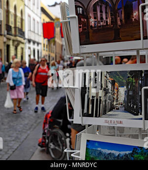 Tourists wander past racks of postcards in the town of Santa Cruz on the Canary Island of La Palma. - Stock Photo