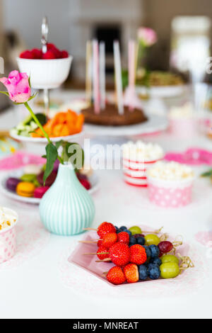 Cake,  candies,  marshmallows,  popcorn,  fruits and other sweets on dessert table at kids birthday party - Stock Photo