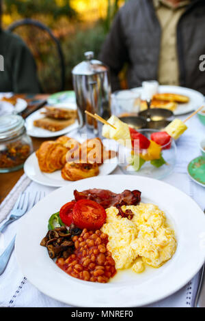 Delicious breakfast with scrambled eggs,  beans,  bacon and vegetables - Stock Photo