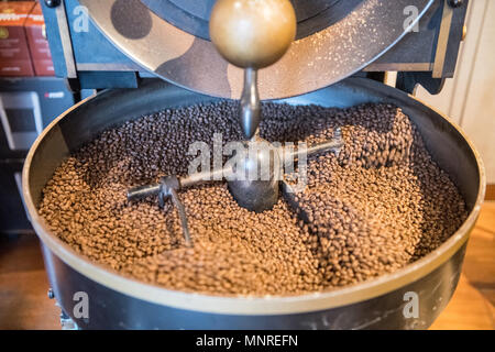 A mechanical arm of a machine slowly rotates freshly roasted coffee beans to cool them down, Istanbul, Turkey - Stock Photo