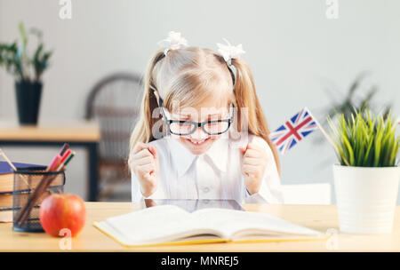 Young happy girl wears white shirt and eyeglasses learning English language with book in light stylish classroom, studying success concept - Stock Photo