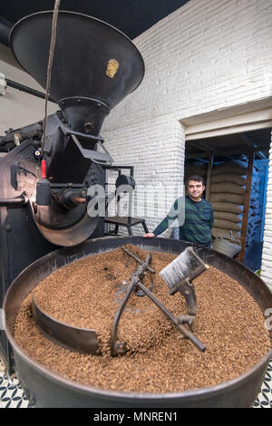 Adult male leans against coffee bean roaster as a mechanical arm slowly rotates freshly roasted coffee beans to cool them down, Istanbul, Turkey. - Stock Photo