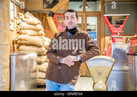 Adult male merchant leans against weighing scale in coffee shop, Istanbul, Turkey. - Stock Photo