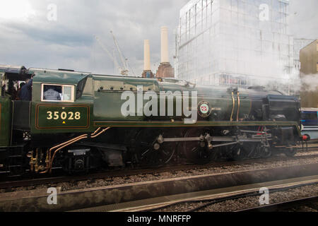A steam engine locomotive  on it's way past the iconic Battersea Power Station in Central London - Stock Photo