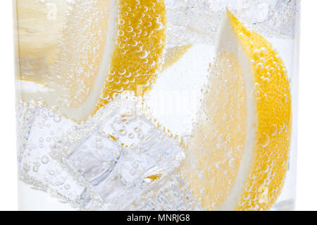 In a glass with cubes of melting ice slices of a juicy lemon. - Stock Photo