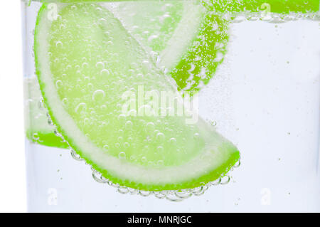 Pieces of fresh juicy lime sink into clear water. - Stock Photo