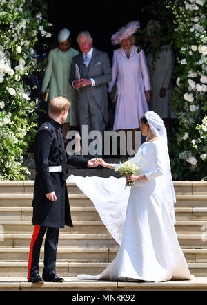 Prince Harry and his wife Meghan turn to watch Meghan Markle's mother Doria Ragland, the Prince of Wales and the Duchess of Cornwall as they walk down the west steps of St George's Chapel, Windsor Castle, after their wedding ceremony. - Stock Photo