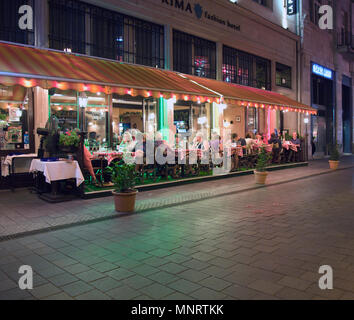 People enjoying dining out at a popular restaurant in the Vaci pedestrian area of downtown Pest, Budapest, Hungary. - Stock Photo