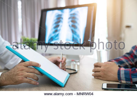 Close up of doctor filling up an application form while consulting patient - Stock Photo