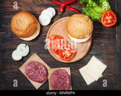 Homemade hamburger ingredients. Raw minced beef, fresh bun, slice of cheese, tomato, onion rings, lettuce on wood background. - Stock Photo