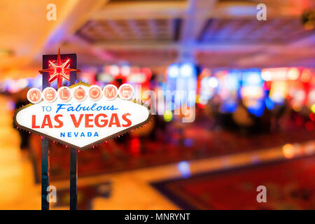 Famous Las Vegas sign at night with casino blur background. - Stock Photo