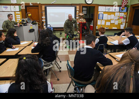 Wash. (March 14, 2018) -- Navy Diver 1st Class Jason Peters, from Panama City, Florida, assigned to Puget Sound Naval Shipyard and Intermediate Maintenance Facility's Everett dive locker, gives a Science, Technology, Engineering and Math - Art + Design (STEAM) presentation about how science and math are factored into the process of diving to a group of students at Immaculate Conception and Our Lady Of Perpetual Help School. STEAM is a program that teaches children the importance of science, technology, engineering, math, art and design in the everday world, and opens their eyes to possible car - Stock Photo
