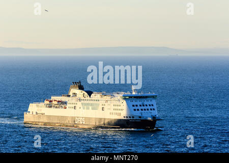England, Dover harbour. DFDS 'Cote des Flandres' car ferry sailing across English Channel. French coast in background. Dawn. - Stock Photo