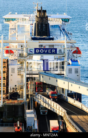 England, Dover harbour. DFDS 'Cote des Flandres' car ferry at terminal unloading trucks in the golden hour early morning. - Stock Photo