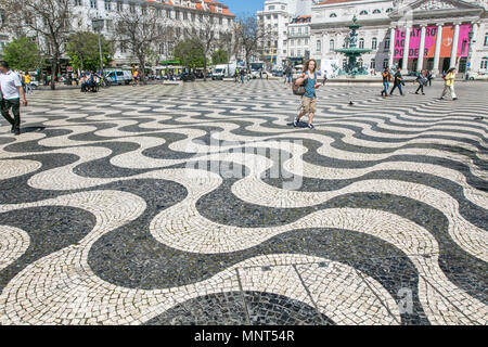 Lisbon, Portugal, May 5 2018 People walk across Rossio Square - Stock Photo
