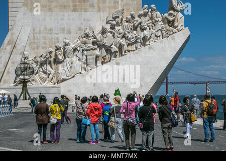 Asian tourists are taking pictures in front of the Monument to Discoveries in Belem, Lisbon, Portugal. - Stock Photo
