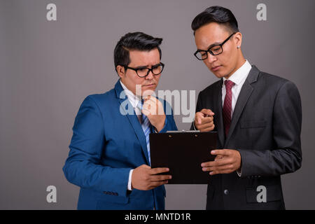 Young multi-ethnic businessman and young Indian businessman agai - Stock Photo