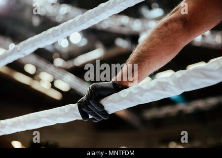 referee hand in black glove on white ropes of ring - Stock Photo