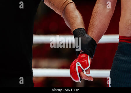 hands of referee and MMA fighter after fight announcement ceremony of winner - Stock Photo