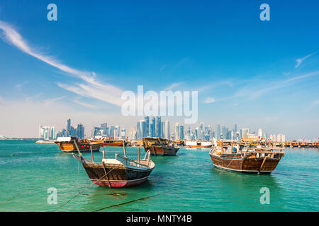 Waterfront in Doha Qatar with traditional wooden small ships known as dhow and city skyline - Stock Photo