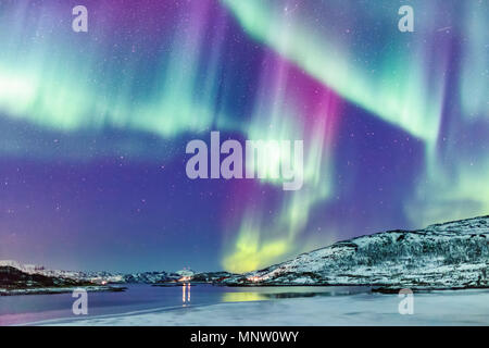 Incredible Northern lights Aurora Borealis activity above the coast in Norway - Stock Photo