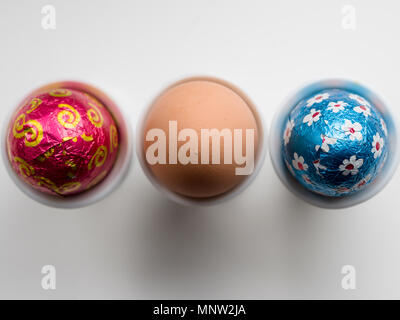Chocolate Easter Eggs and a brown hen's egg in egg cups: A row of three eggs in three white porcelain egg cups on a white background. - Stock Photo