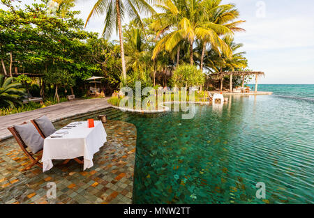 Romantic luxury dinner setting  near infinity swimming pool at tropical resort on sunset - Stock Photo