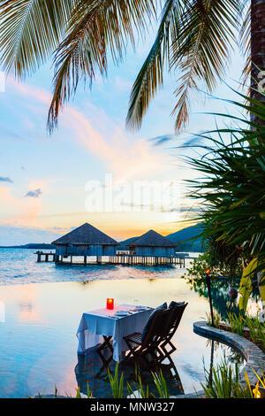 Romantic luxury dinner setting at tropical resort on sunset - Stock Photo