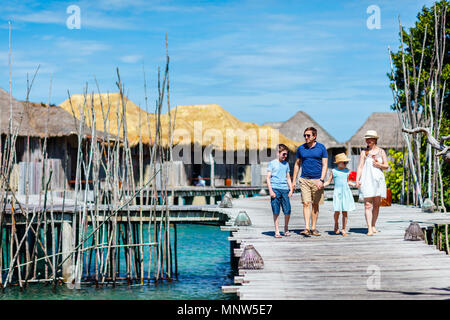 Happy beautiful family walking on wooden jetty during summer vacation at luxury resort - Stock Photo